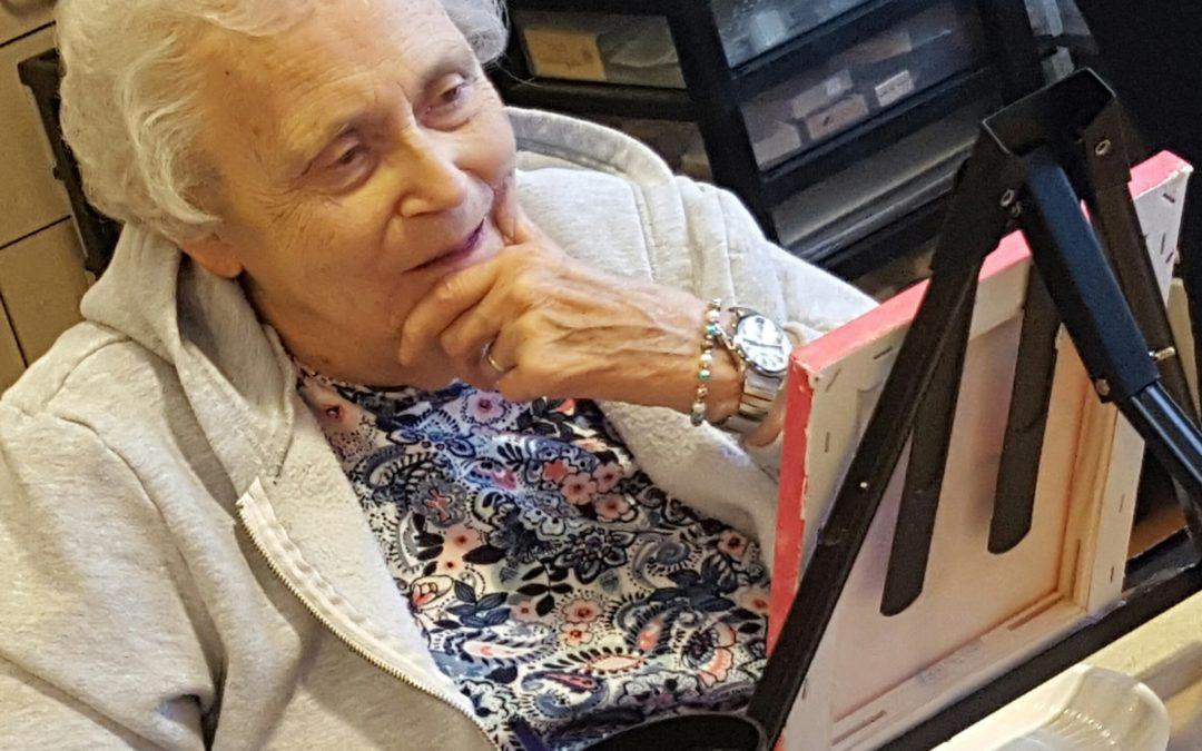 Resident Jacquelyn Hudak admires her painting.